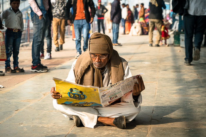 Man reading newspaper on Indian train platform.